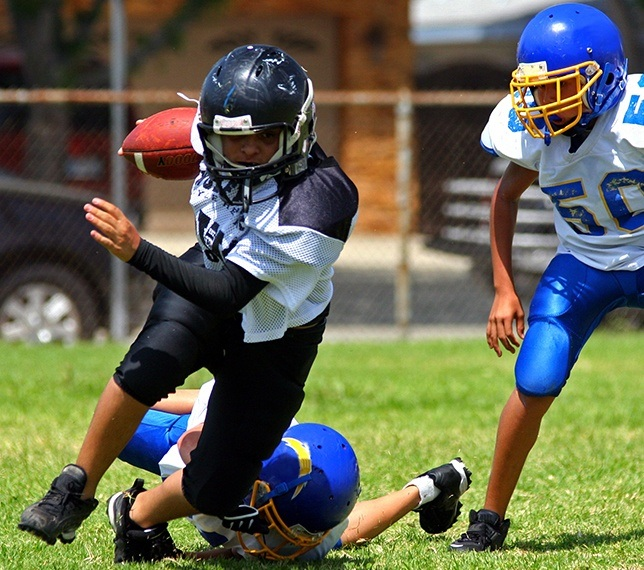 Teens playing football with athletic mouthguard in place