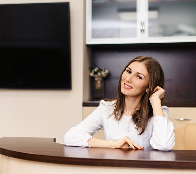 A female dental receptionist sitting behind a desk and smiling