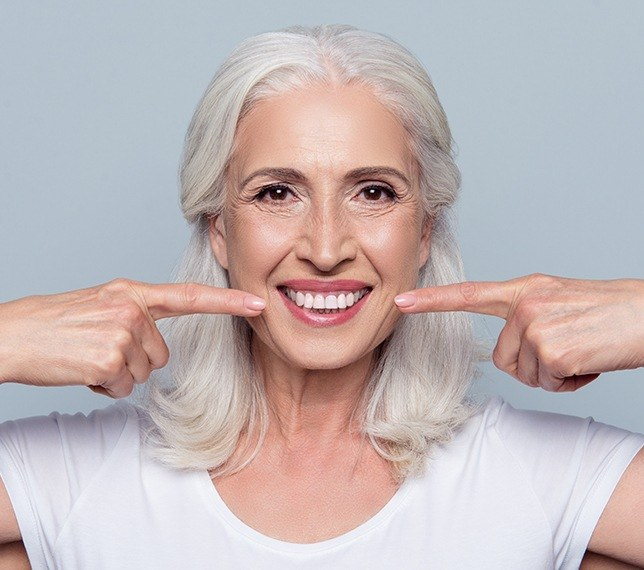 Woman pointing to healthy smile after scaling and root planing periodontal therapy